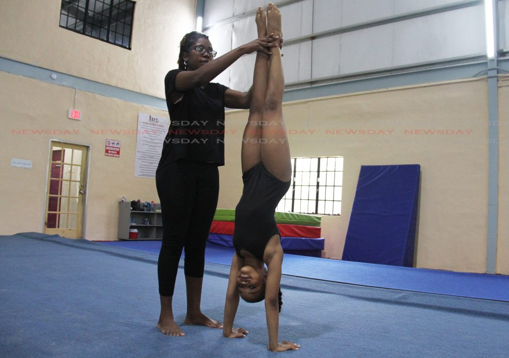 Coach Afeisha Burke assists Jodie Sifontes with her handstand at the House of Gymnastics, Mt Lamber.  Photo: Ayanna Kinsale