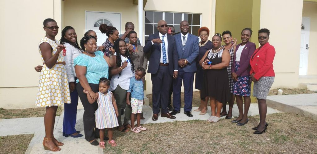 PROUD BUNCH: New home-owners show off their keys alongside Chief Secretary Kelvin Charles at a distribution ceremony on April 8. The home-owners were told to return the keys afterwards.