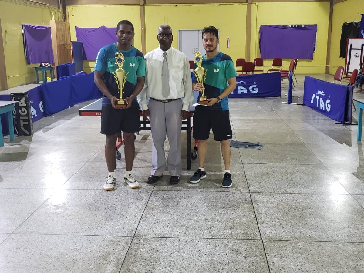 Curtis Humphreys,left, and Kenneth Parmanand,right display their awards after claiming the top prizes, at the WASA Tag Team table tennis tournament, on Sunday, at the WASA grounds, St Joseph. At centre, is former coach Roland Charles.