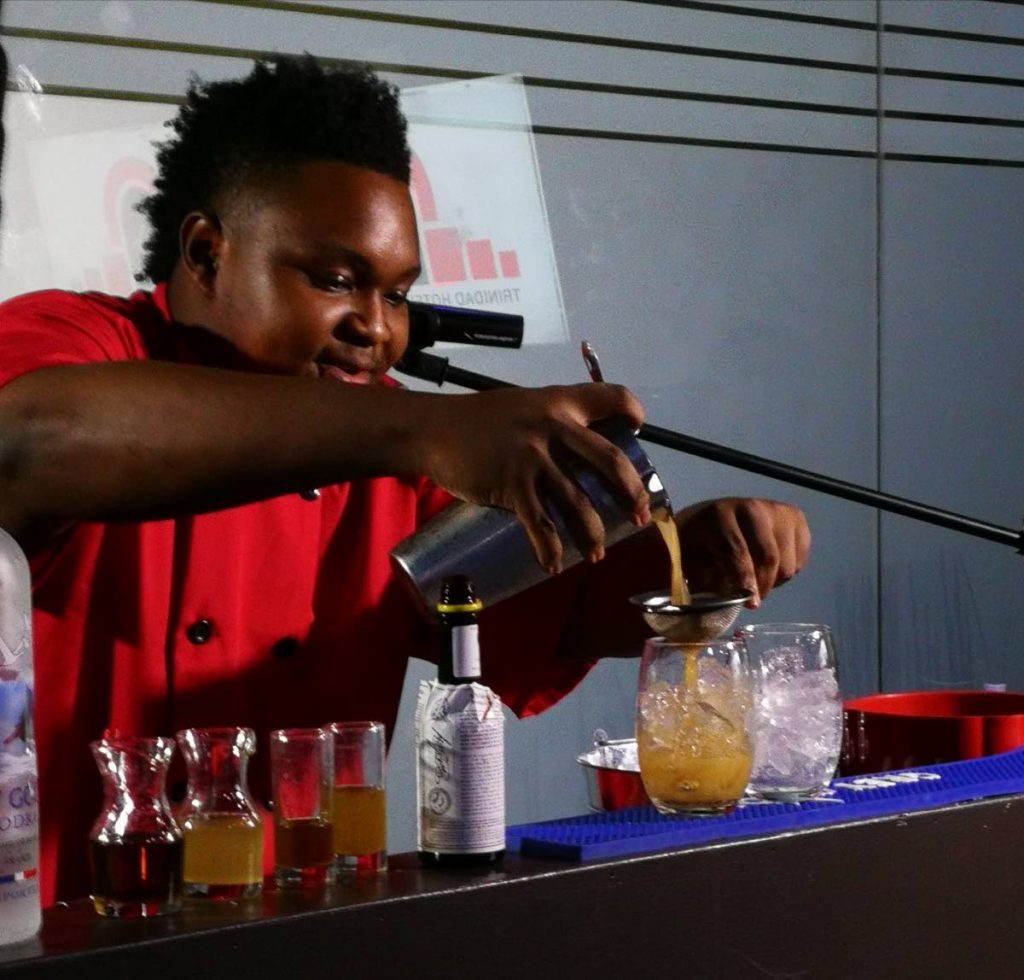 MR MIXER: Isaiah Trumpet mixes a cocktail en route to copping a silver medal for himself and team TT at a culinary competition held in Miami. The team also copped a gold and silver in other events.
