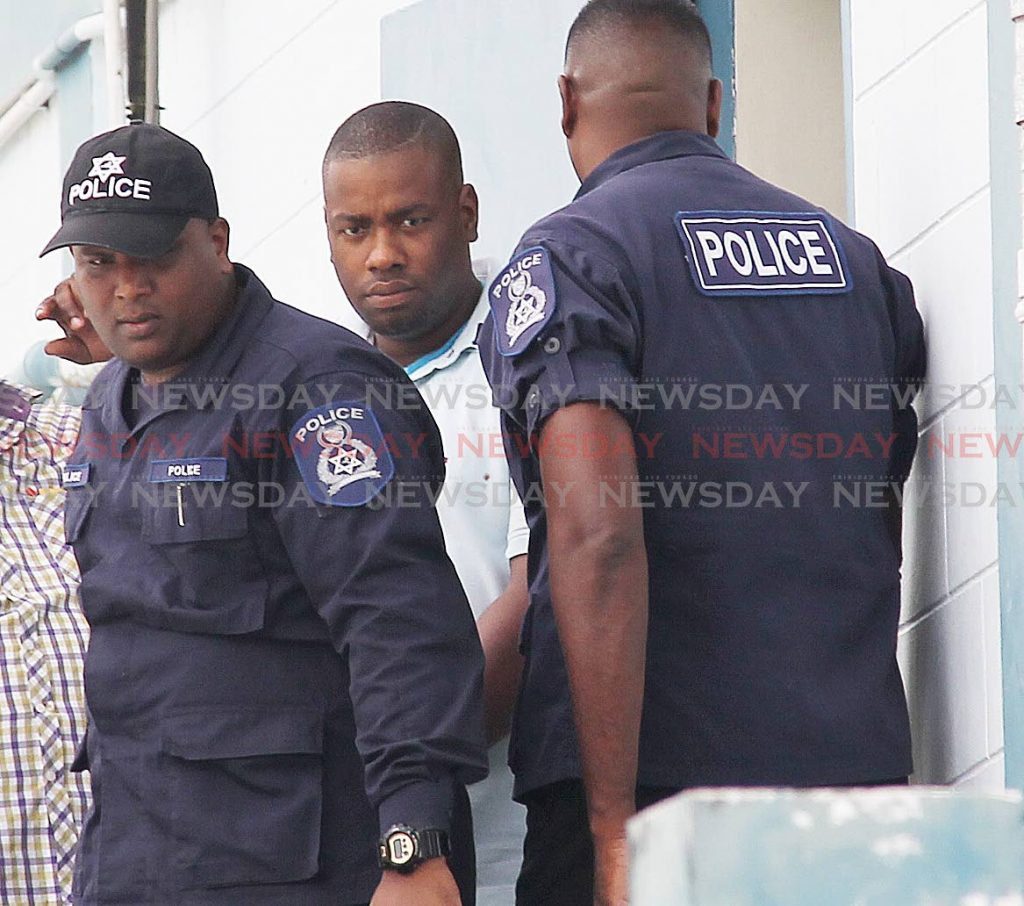 Special reserve police officer Akeem James, centre, is escorted to the Rio Claro court house to appear before a Princes Town magistrate to answer charges of raping and kidnapping a Venezuelan woman in November of 2018. He was denied bail. PHOTO BY LINCOLN HOLDER