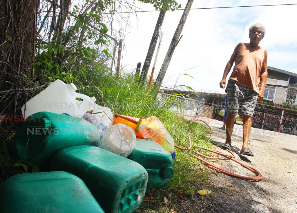 Resident Austin LeGendre fills containers at a standpipe along the Naparima/Mayaro main road, Tableland, as community households have been without pipeborne water for over a month. PHOTO BY LINCOLN HOLDER