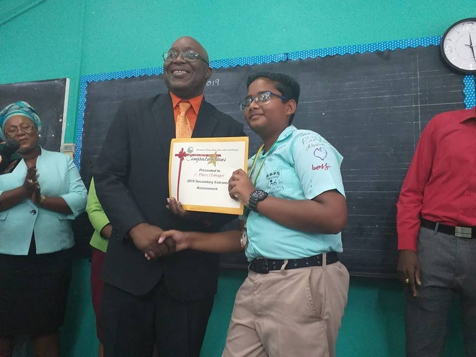 TOP IN TOBAGO: Sebastian Rampersad is congratulated by THA Chief Secretary Kelvin Charles after it was announced that the Buccoo Govt Primary School student topped the sister isle in the 2019 SEA exam results. PHOTO COURTESY OFFICE OF THA CHIEF SECRETARY