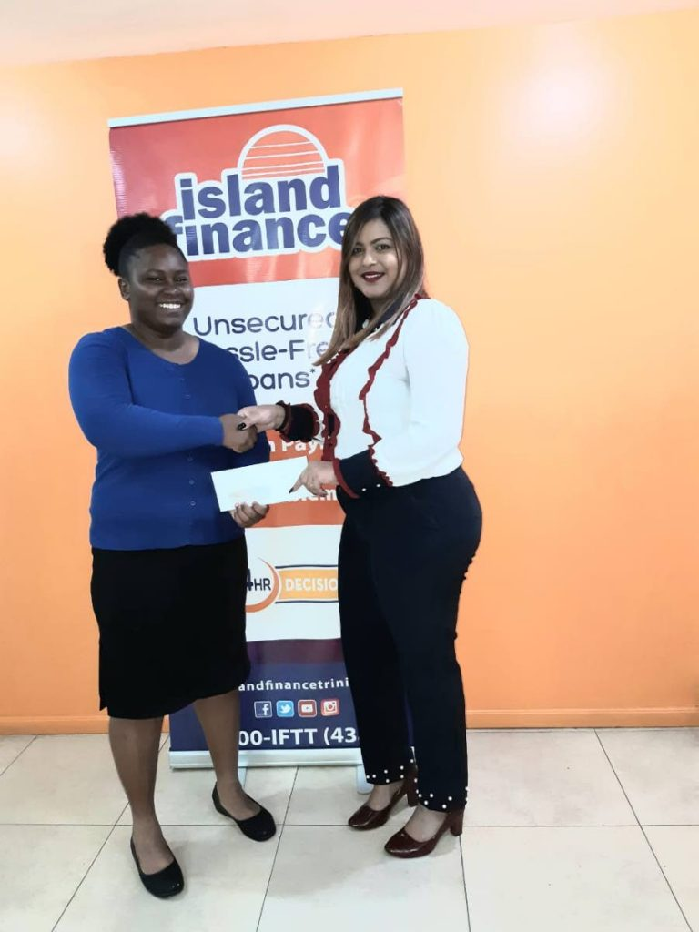 Makeisha Simon, 21, left, receives a cheque from Island Finance's assistant vice-president Rehana Khan at its Princes Town branch on Friday. PHOTO COURTESY REHANA HOSEIN