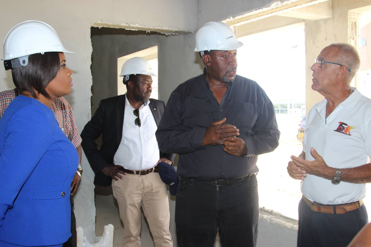 Sports Company chairman Douglas Camacho (right) in discussion with TTFA president David John-Williams (second from right) and Sports Minister Shamfa Cudjoe (left) during a visit at the Home of Football, in Balmain, Couva on August 19 2018. In the background, FIFA representative Veron Mosengo-Oba looks on.