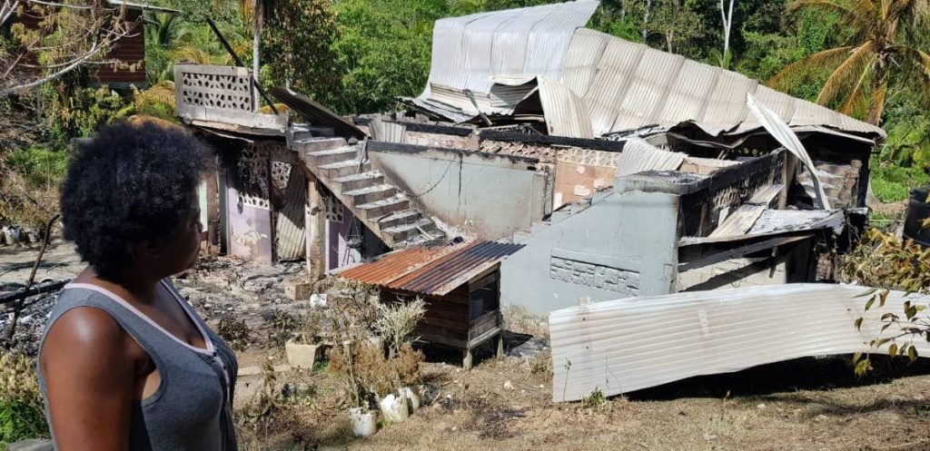 In this March 26 file photo, Pat McIntyre-Prince looks at the ruins of her family's house after it was destroyed by fire at Happy Hill, Basse Terre Village, Moruga.