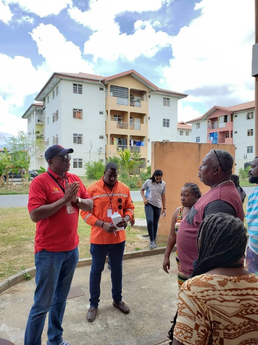 HDC managing director Brent Lyons, left, engages residents of Oropune Gardens, Piarco during an Arouca police community walkabout on Aprill 27.  PHOTO COURTESY HDC