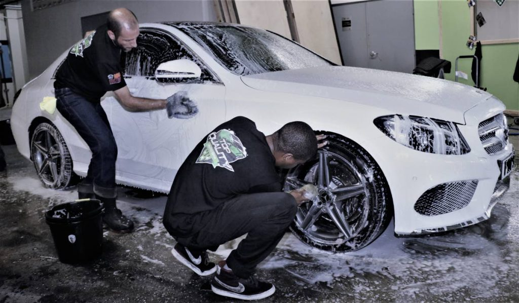 Staff of Top Quality Auto Spa detail a car at the official launch of the business.
