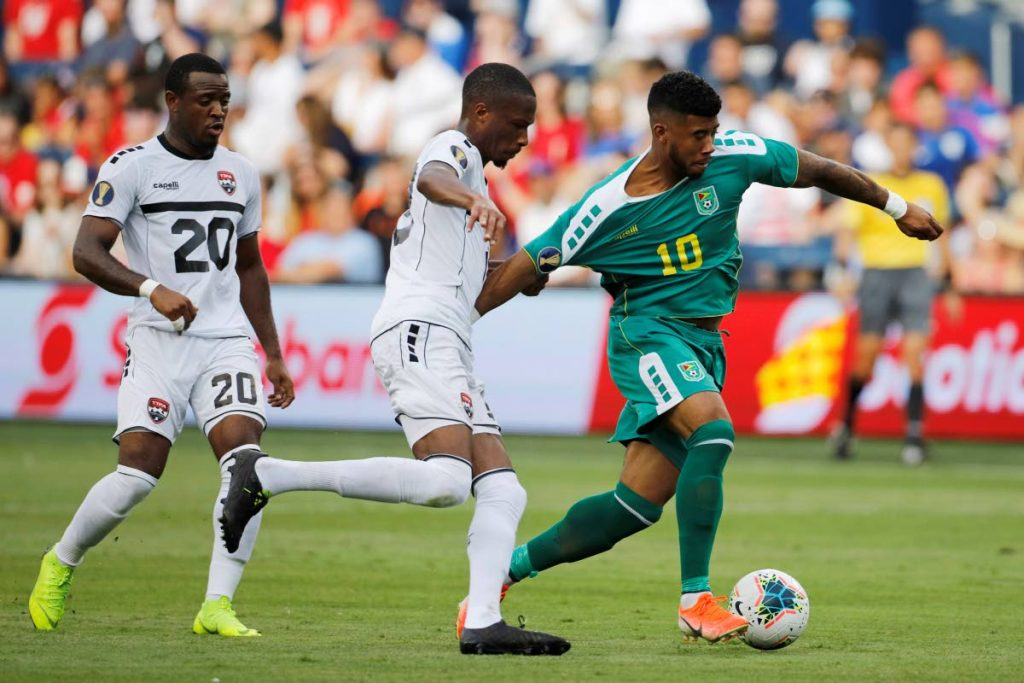 TT midfielder Jomal Williams (20) looks on as defender Curtis Gonzales, centre, holds the jersey of Guyana forward Emery Welshman (10) during the second half of a Concacaf Gold Cup match in Kansas City, Kan, on June 26. The match ended 1-1. AP Photo