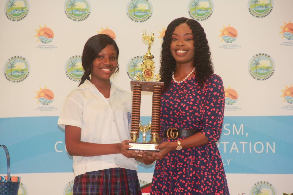 Scarborough Secondary's Kayleigh Lewis, left, collects a trophy after being crowned 2019 Tourism Youth Congress Junior Secretary. The award was presented by Secretary for Tourism Nadine Stewart-Phillips at the Scarborough Library last Friday.