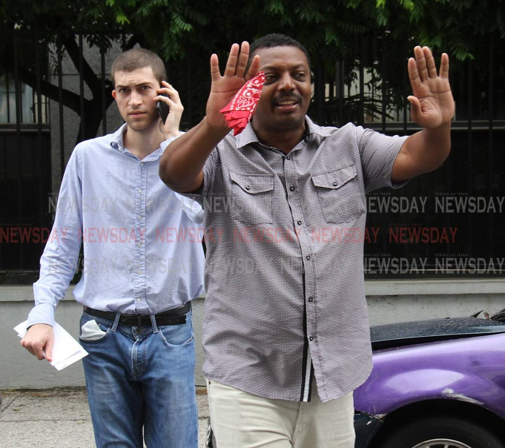 A man attempts to block the media from taking photographs of Elias Aboud, left, as he makes his way to the Port of Spain Magistrates' Court where he appeared on charges of possession of marijuana and narcotic related offences. Photo by Angelo Marcelle