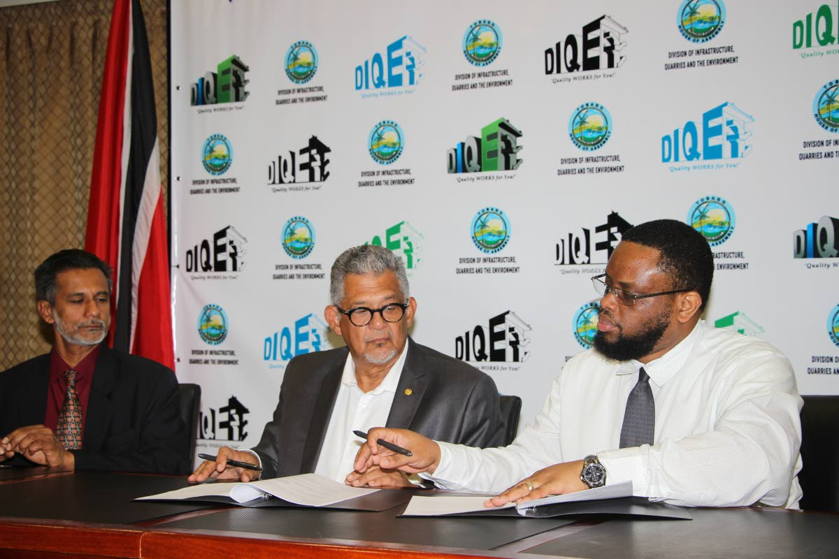 SIGNED: THA's Department of Infrastructure Quarries and the Environment's Richie Toppin signs the MoU as PTSC GM Bashir Mohammed, left, and chairman Edwin Gooding look on.