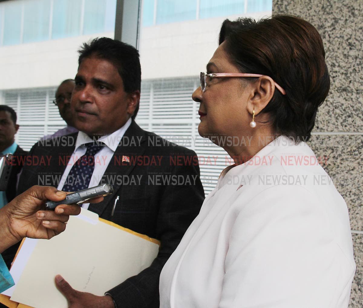Opposition Leader Kamla Persad-Bissessar and Oropouche East MP Dr Roodal Moonilal speak with media outside Parliament in Port of Spain, on Wednesday. PHOTO BY ANGELO M MARCELLE
