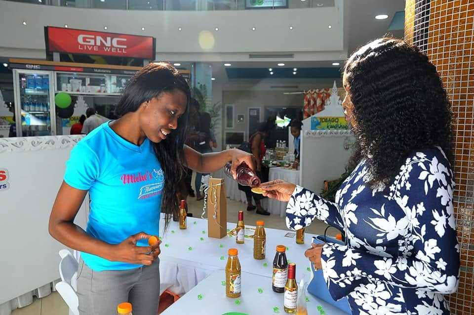 Michelle gives a sample of her pepper sauce to THA Secretary of Tourism, Culture and Transportation, Nadine Stewart-Phillips during her recent stint at the THA-hosted Tobago Road Show at Trinity Mall.