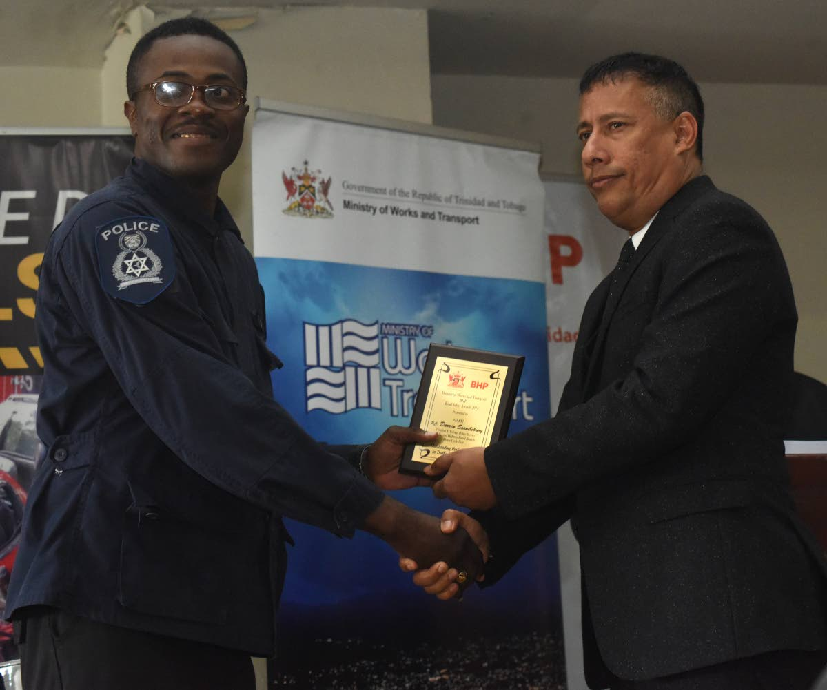 WELL DONE: Police Commissioner Gary Griffith presents an award to PC Darren Scantlebury of the Highway Patrol Branch during a road safety awards ceremony on Wednesday at the Ministry of Works and Transport in Port of Spain. PHOTO BY KERWIN PIERRE