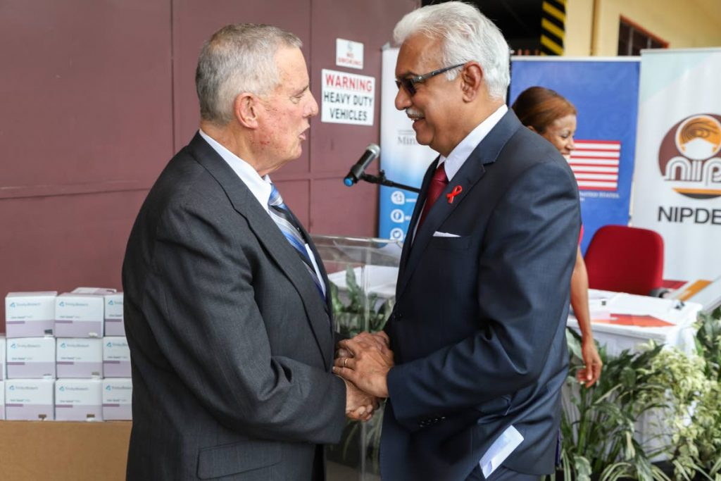 GREETINGS: US Ambassador Joseph Mondello, left, shakes hands with Health Minister Terrence Deyalsingh on Wednesday after the handing over of HIV test kits to the ministry at the Nipdec central stores in Chaguaramas.