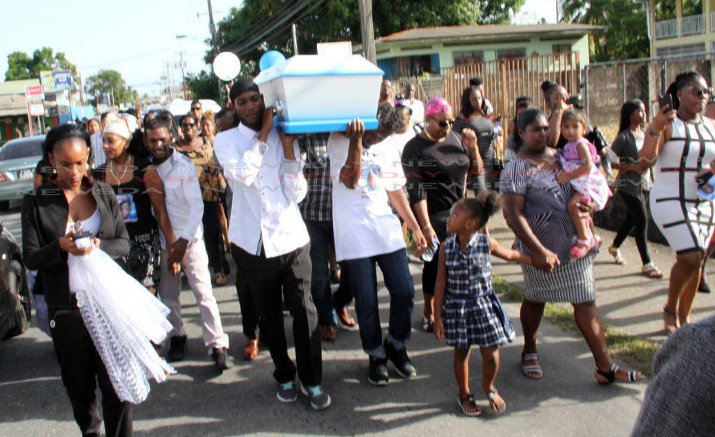 Pall bearers carry the body of little Isaiah Hazel to the cemetery after the funeral at Mt Moriah Spiritual Baptist Church, Yallery Street, Couva, on Wednesday.   PHOTO BY VASHTI SINGH