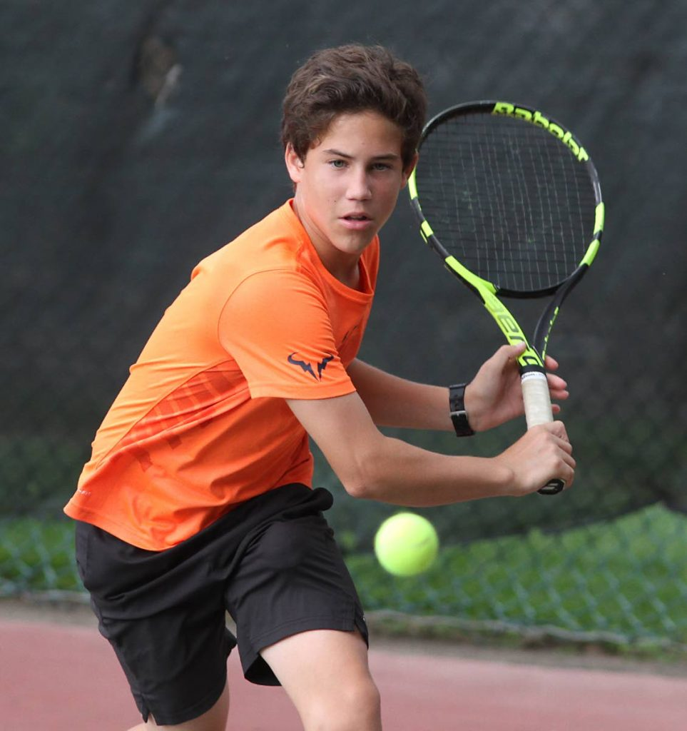 Daniel Jeary attempts a backhand against Kale Dalla Costa in the  boys 14 and under singles final, at the Sagicor Junior Tennis Tournament, Trinidad Country Club, Maraval, yesterday. Dalla Costa won the contest 6-4, 6-4.
