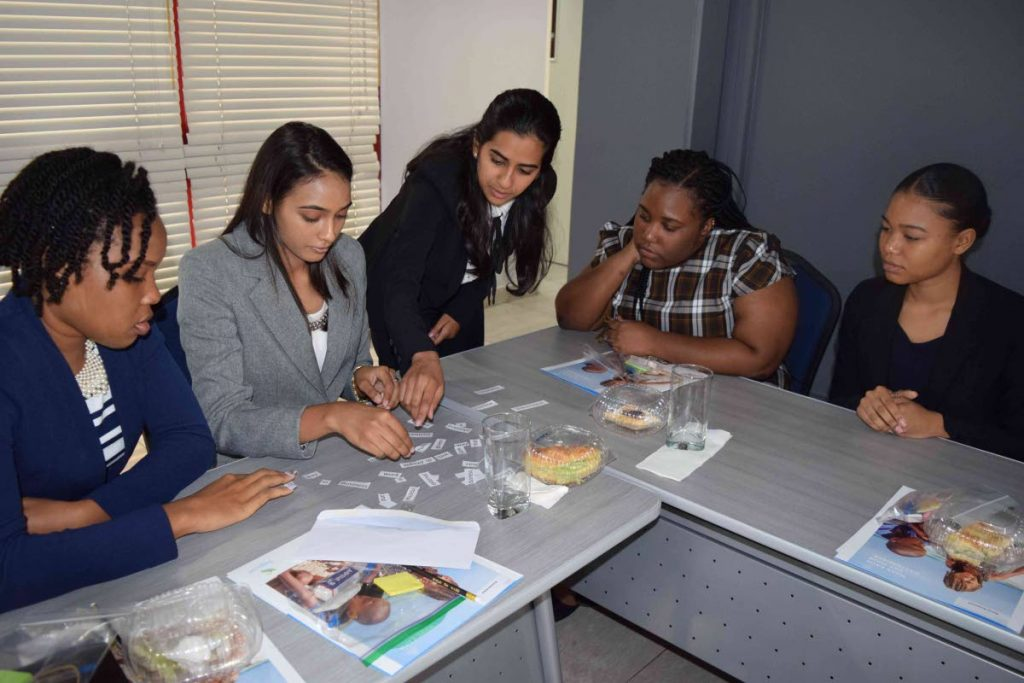 GETTING DOWN TO BRASS TACKS: Some interns work on a group activity during their orientation session at Sagicor's Port of Spain office. PHOTO COURTESY SAGICOR