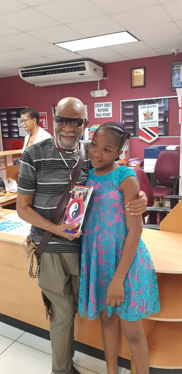 Bill Trotman presents an autographed copy of his book of poems to a youth at the  library.   Bill Trotman presents an autographed copy of his book of poems to a youth at the  library.