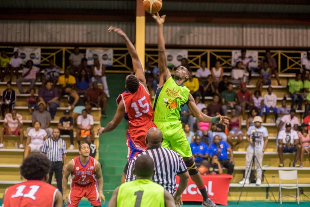 LJ Northside Stingerz's Moriba De Freitas,right, jumps for the ball against a F&G Trading Cutie's Oval Ojays, in the final of the Digicel Antigua and Barbuda Basketball Association Division I league recently.