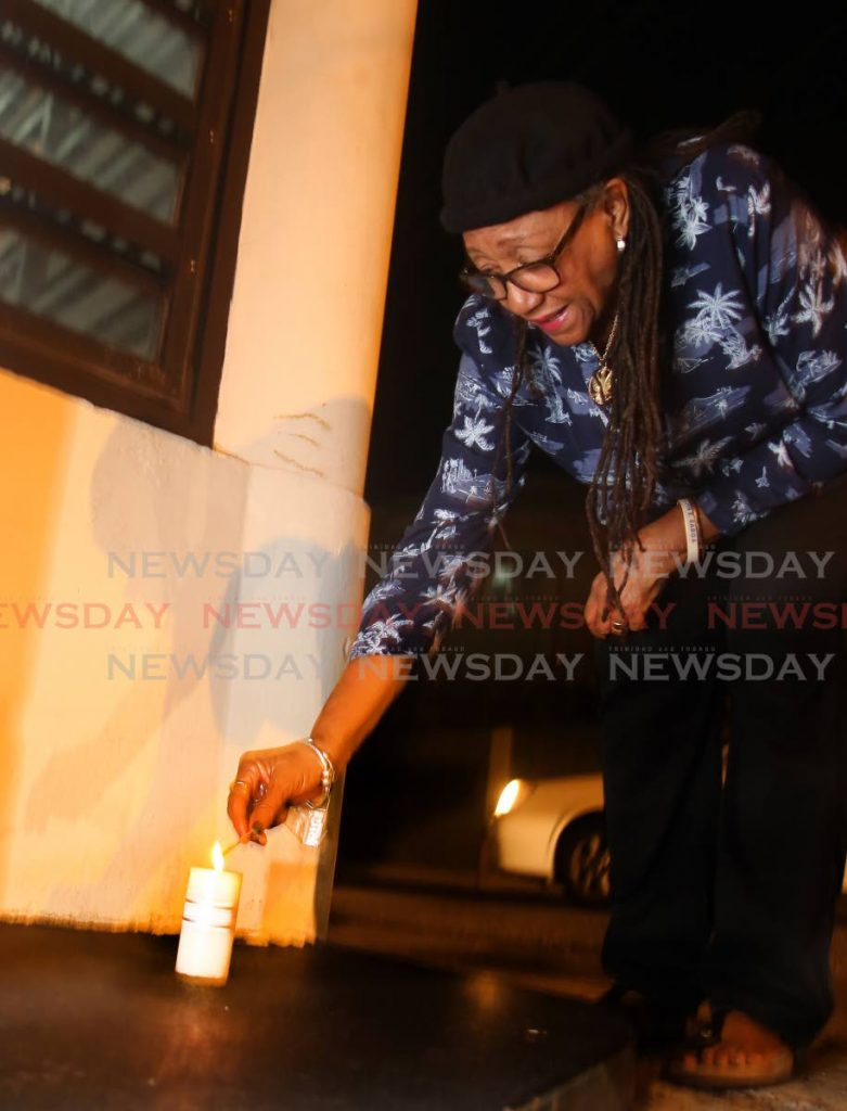 Songstress Mavis John lighs a candle outside the Little Carib Theatre in Woodbrook in memory of slain actor/director Raymond Choo Kong on Monday. PHOTO SUREASH CHOLAI