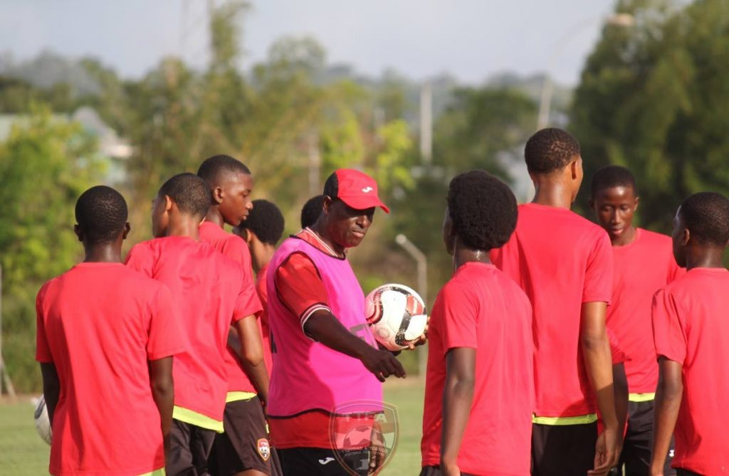 Stuart Charles-Fevrier,centre, talks with members of the TT Under-15 boys team, during a training session prior to the TT Football Association's Youth Invitational,which begins tomorrow.