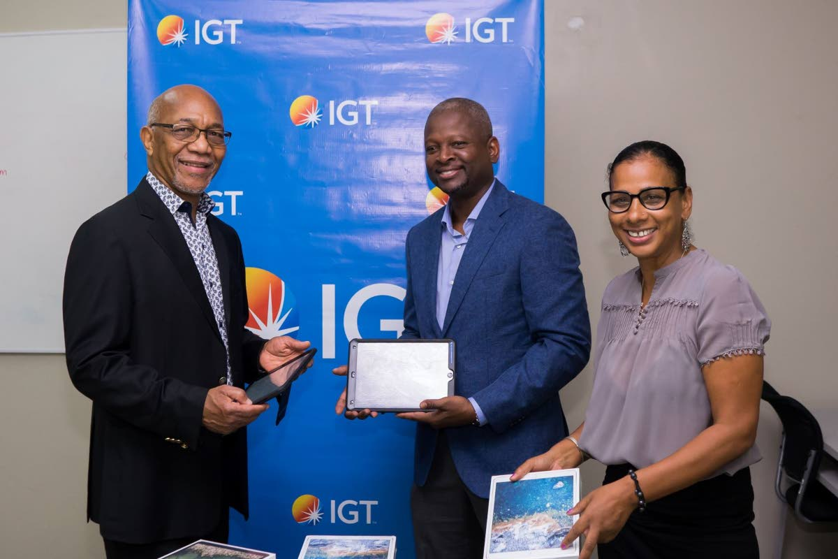 Samuel Martin, chairman of the Cotton Tree Foundation, left, shares a moment with Dexter W Thomas, IGT's deputy country manager, and Miriam Davis, manager of the Cotton Tree Foundation, at the handover ceremony.