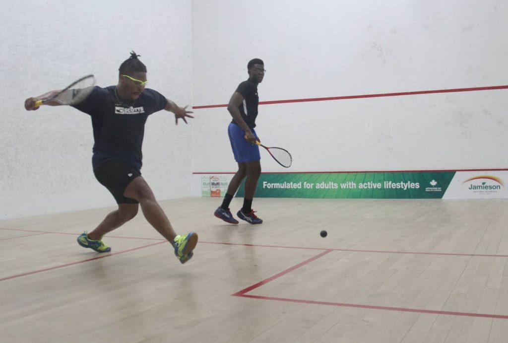 David Pitcairn, left, of Cayman Islands and Khamal Cumberbatch of Barbados at the 2019 Junior Caribbean Area Squash Association (CASA) Championships, yesterday. Cumberbatch won 11-3, 11-5, 11-2. PHOTO BY AYANNA KINSALE