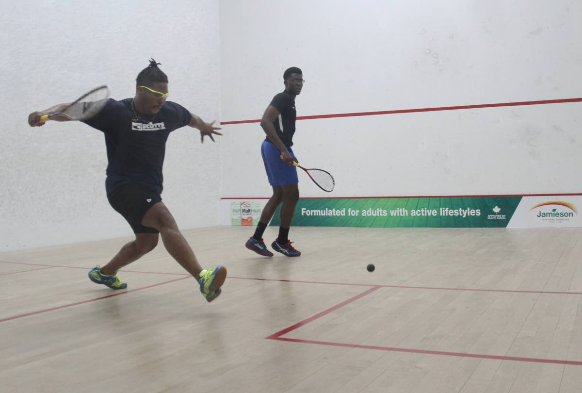 David Pitcairn, left, of Cayman Islands and Khamal Cumberbatch of Barbados at the 2019 Junior Caribbean Area Squash Association (CASA) Championships, yesterday. Cumberbatch won 11-3, 11-5, 11-2. PHOTO BY AYANNA KINSALE