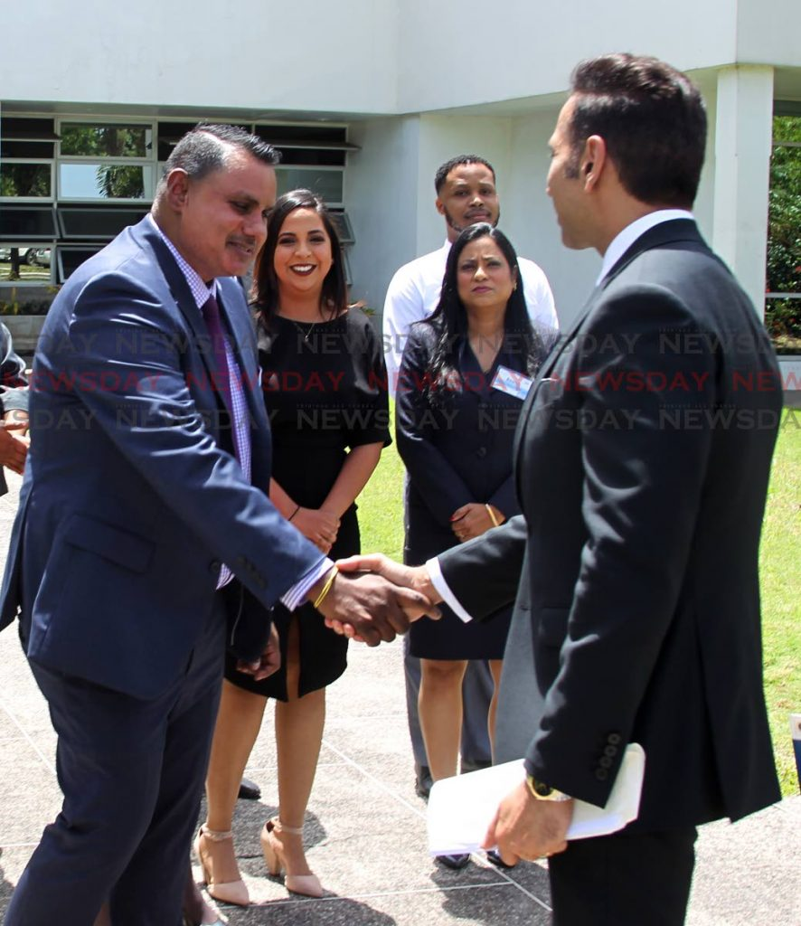 Attorney General Faris Al-Rawigreets programme facilitator Kelvin Ramkissoon, attorney at law, alongside student participants, at the Certificate in Public Procurement Practice programme at the Arthur Lok Jack School of Business, Mt Hope, on Friday. PHOTO BY ROGER JACOB.