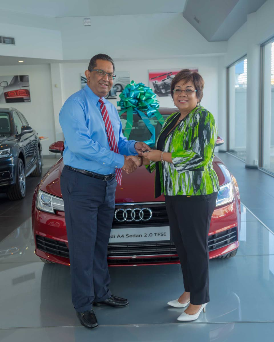 Reyaz Ahamad (left), Director, Southern Sales and Service, hands over the key of the Audi A4 sedan to Marlene Chin, Assistant Vice President, Marketing, Communications and Brand Experience, Sagicor Life Inc. The sedan is the Hole in One prize for Hole 7.