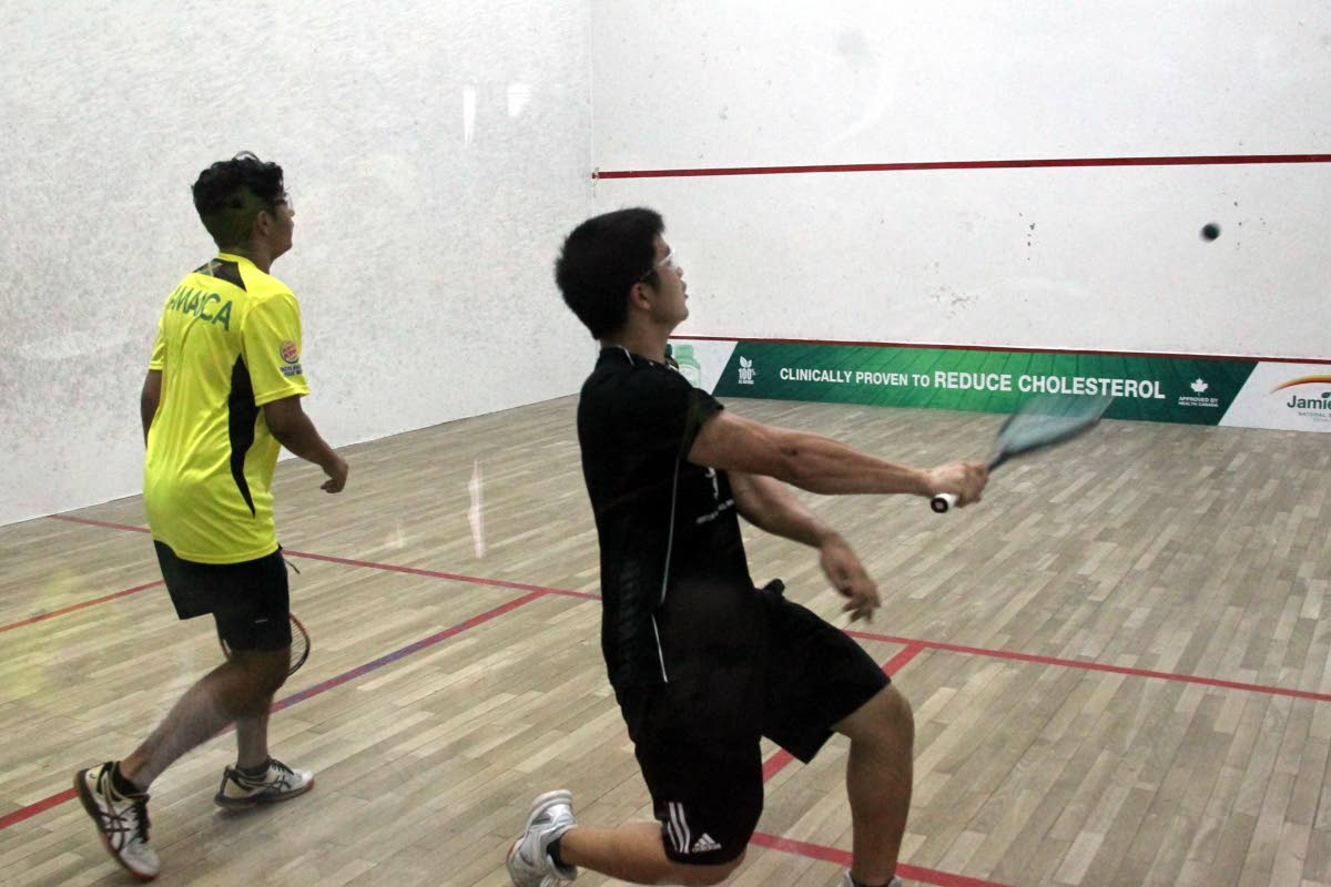 Michael Chin Lee of TT, right, plays Karan Chatani of Jamaica at the 2019 Junior Caribbean  Area Squash Association Championships at the Queen's Park Indoor Racquet Centre in  St Clair. PHOTO BY ROGER JACOB