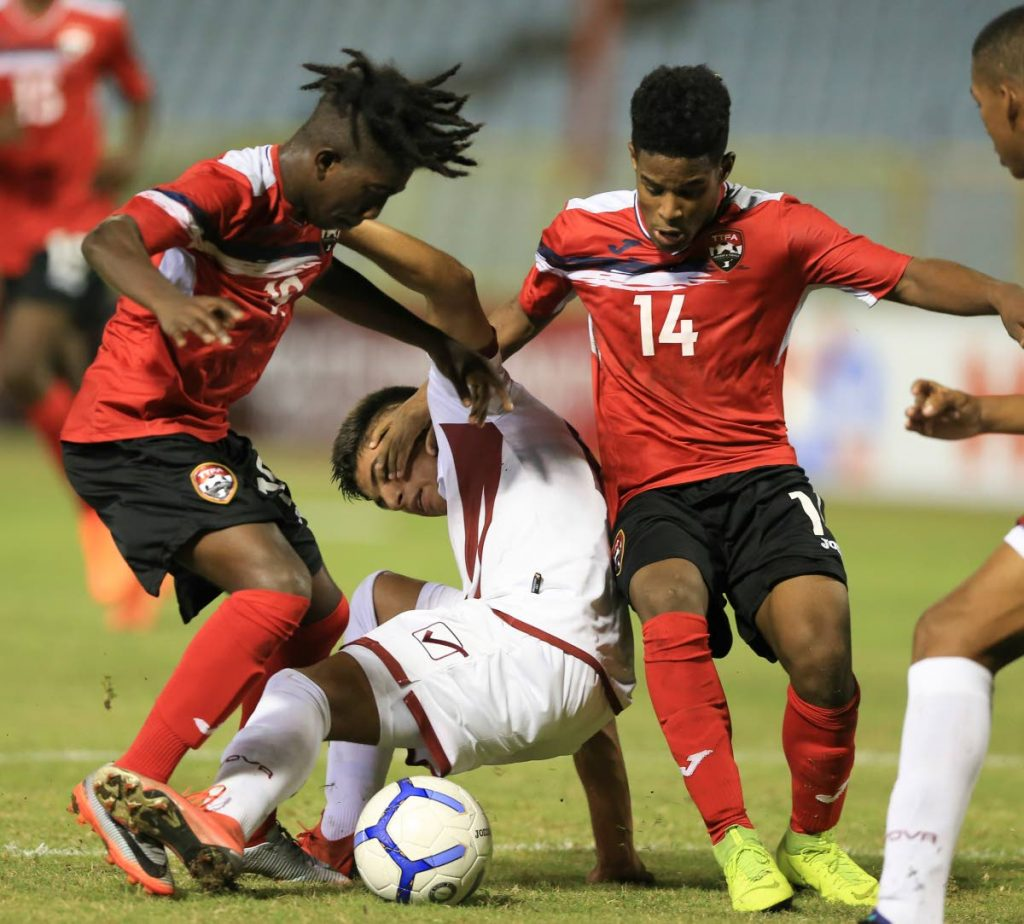 TT's Isaiah Thompson,left, and Jovonn Gomes,right, sandwich Venezuela defender Santiago Tarono, during day 2, match 2 of the TTFA Youth Invitational Tournament Boys U15 between TT and Venezuela at the Hasely Crawford Stadium, Mucurapo,on Friday.