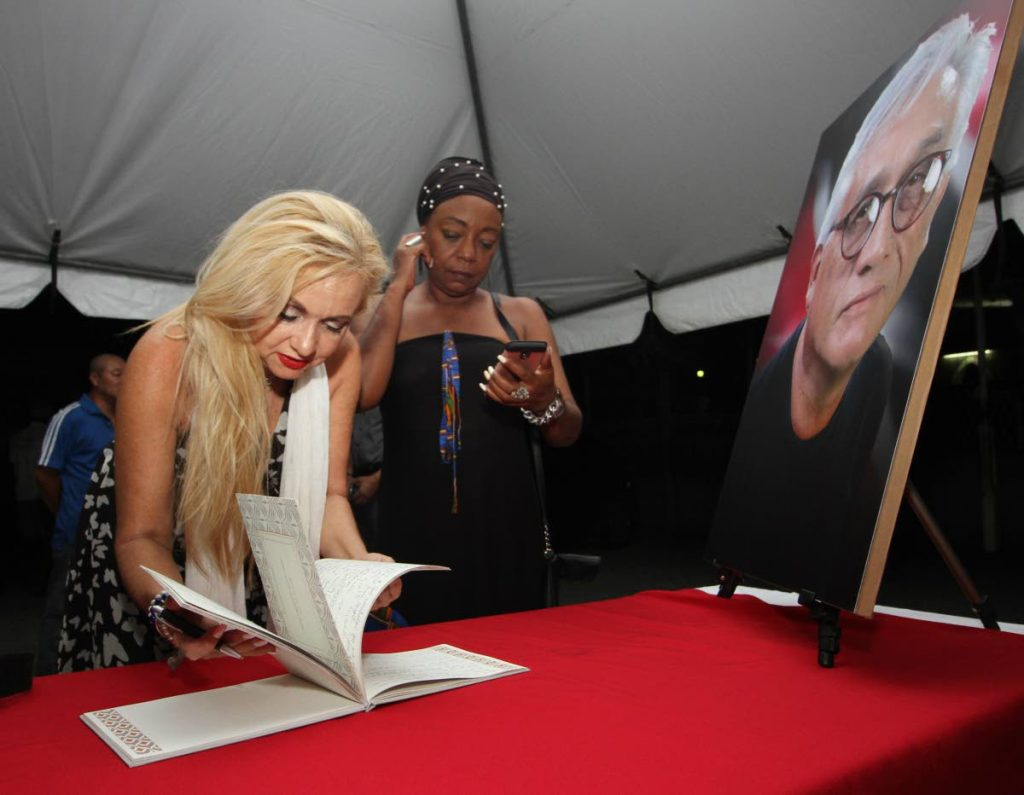Cecilia Salazar, signs the condolence book at the wake for slain actor Raymond Choo Kong at the Arima Boys RC Primary School Penelope Spencer looks on.