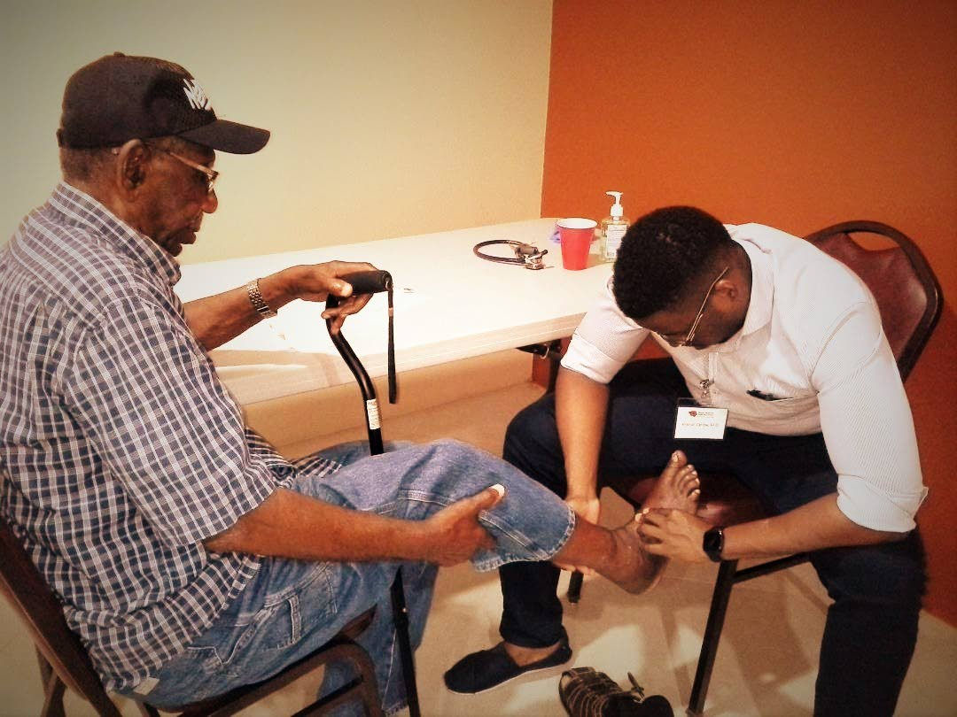 A member of the community gets his feet checked by Dr Mikhail Carlow at the Adult Day Centre health fair in Bon Accord.