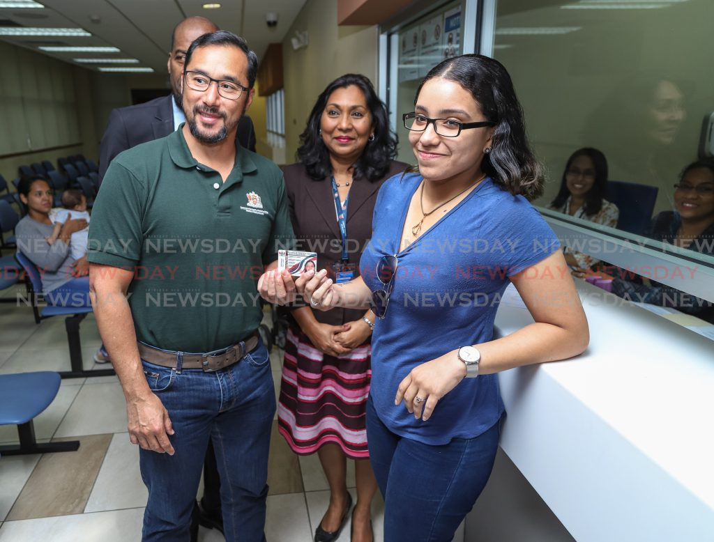 Minister of National Security Stuart Young and Venezuelan Karen Betzabeth Corrales Corvo as she displays her registration card at the Immigration Division office. Also in the photo is chief immigration officer Charmaine Gandhi-Andrew in July.  Photo: Jeff K Mayers