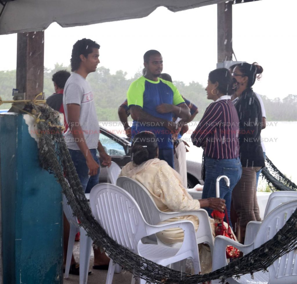 Villagers and relatives wait for news of three missing fishermen at Orange Valley yesterday.