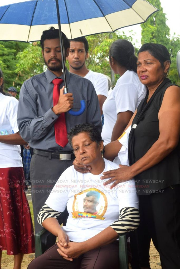 DAZED: Samoo Ali sits during the funeral for her son, murdereed fisherman Anand
