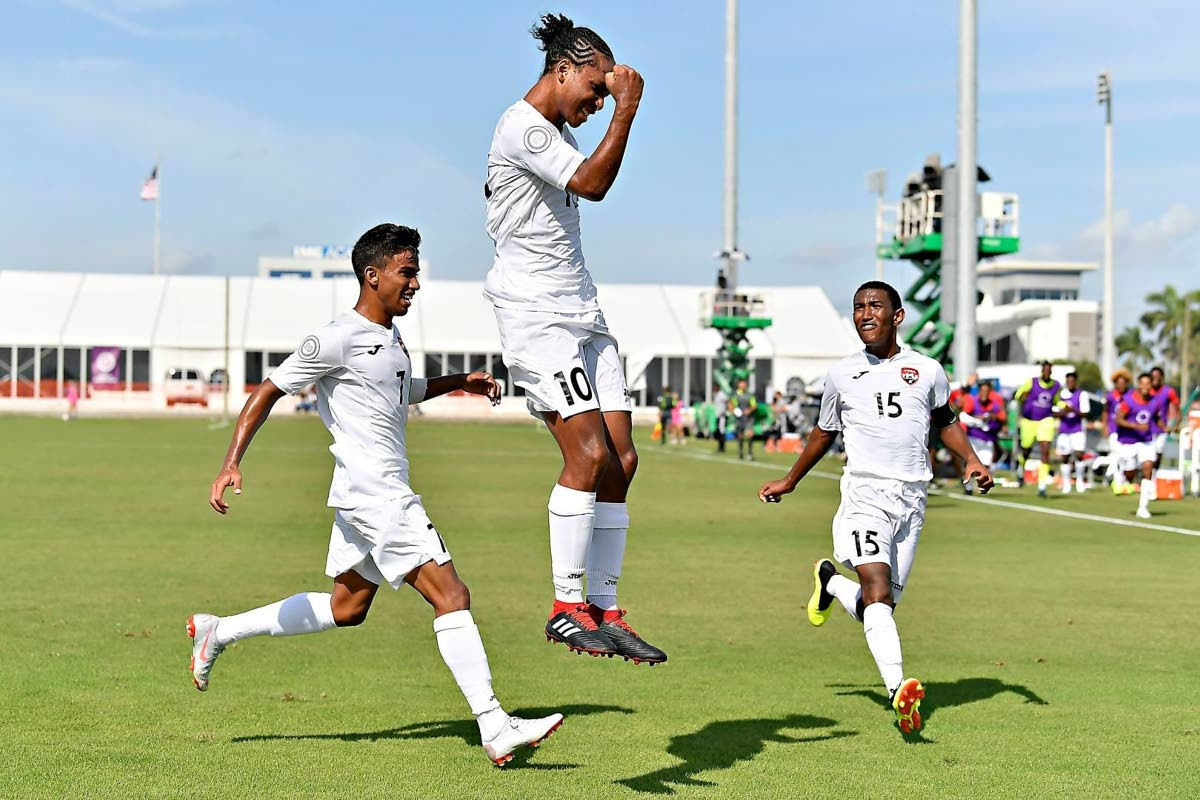TT's Judah Garcia (centre) leaps with a clenched fist as he celebrates his game-winner against St Vincent/Grenadines during a Concacaf Under-20 Championship match last year. Also in photo are Mark Ramdeen (left) and John-Paul Rochford. PHOTO COURTESY CONCACAF.