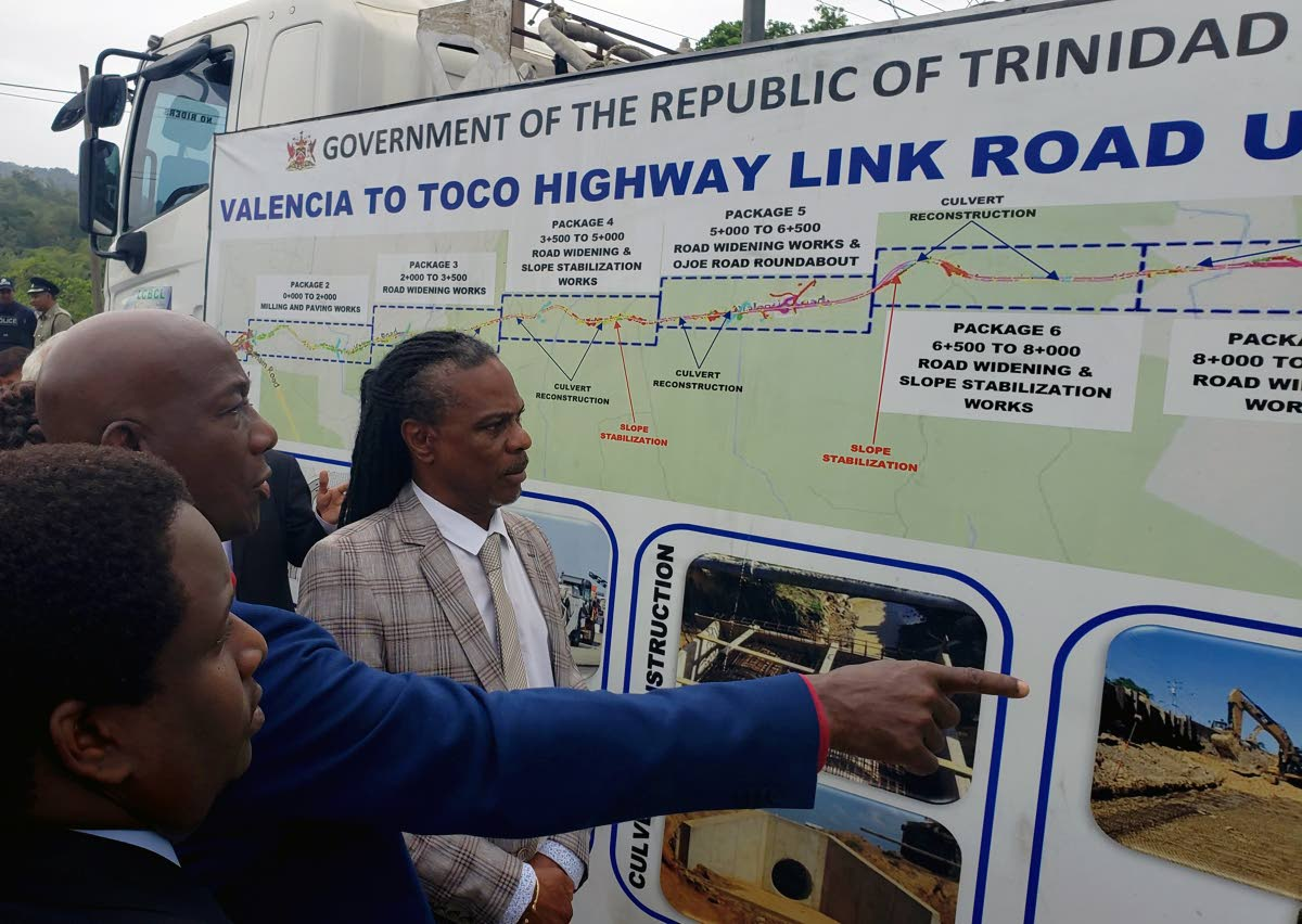 Prime Minister Dr Keith Rowley, centre, Hayden Phillip, director of PURE, right, and Anton Balfour, senior project manager at PURE, left, examine an illustration of the road upgrade projects at the sod-turning ceremony for the Valencia to Toco Highway Link Road, Valencia Main Road, Valencia on March 27. FILE PHOTO