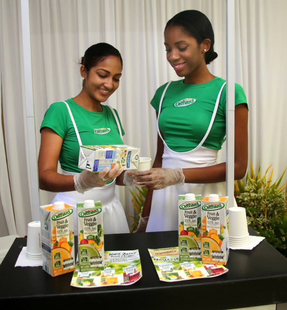 Leanna Samaroo left and Anaya Price pour Nestle Orchard 's new Fruit and Veggie Juice during the product launch at the company's Valsayn compound.