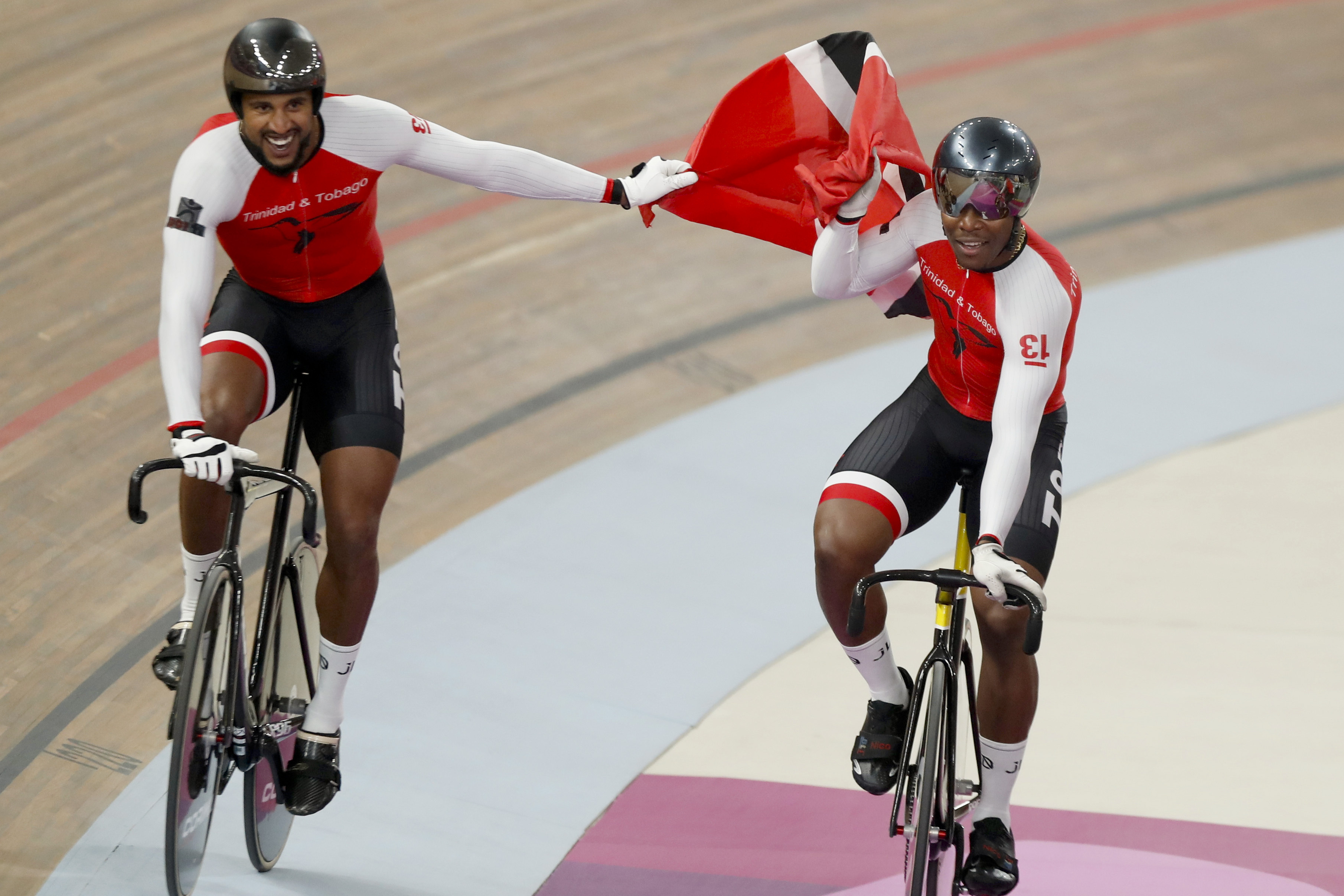 Trinidad and Tobago cycling team members, composed of Keron Bramble, Paul Nicholas and Njisane Phillip, celebrate winning the gold medal in the cycling track men's team sprint at the Pan American Games in Lima, Peru, Thursday, Aug. 1, 2019. (AP Photo/Fernando Llano)