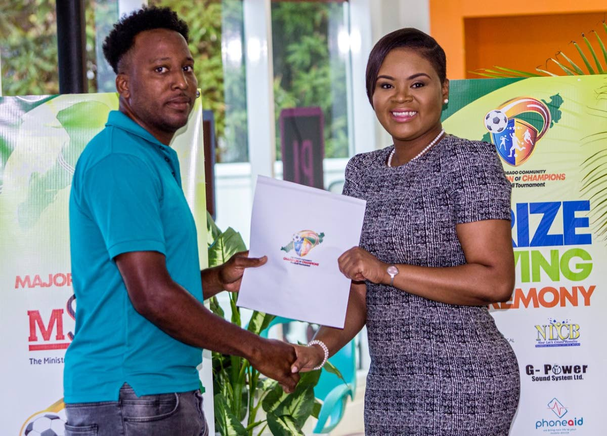 Sports Minister Shamfa Cudjoe distributes prizes for the Tobago Community Champion of Champions Football Tournament at the Orange Business Group Headquarters in Carnbee, last Tuesday.