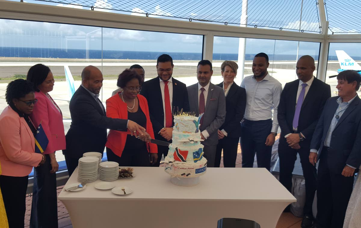 Government and CAL representatives from both Curacao and TT look on as Curacao Transport Minister, Zita Jesus-Leito and Minister of Economic Development, Kenneth Gijsbertha cut a cake at a reception celebrating CAL's inaugural flight to Curacao at the Curacao International Airport on Friday. PHOTO BY JANELLE DE SOUZA