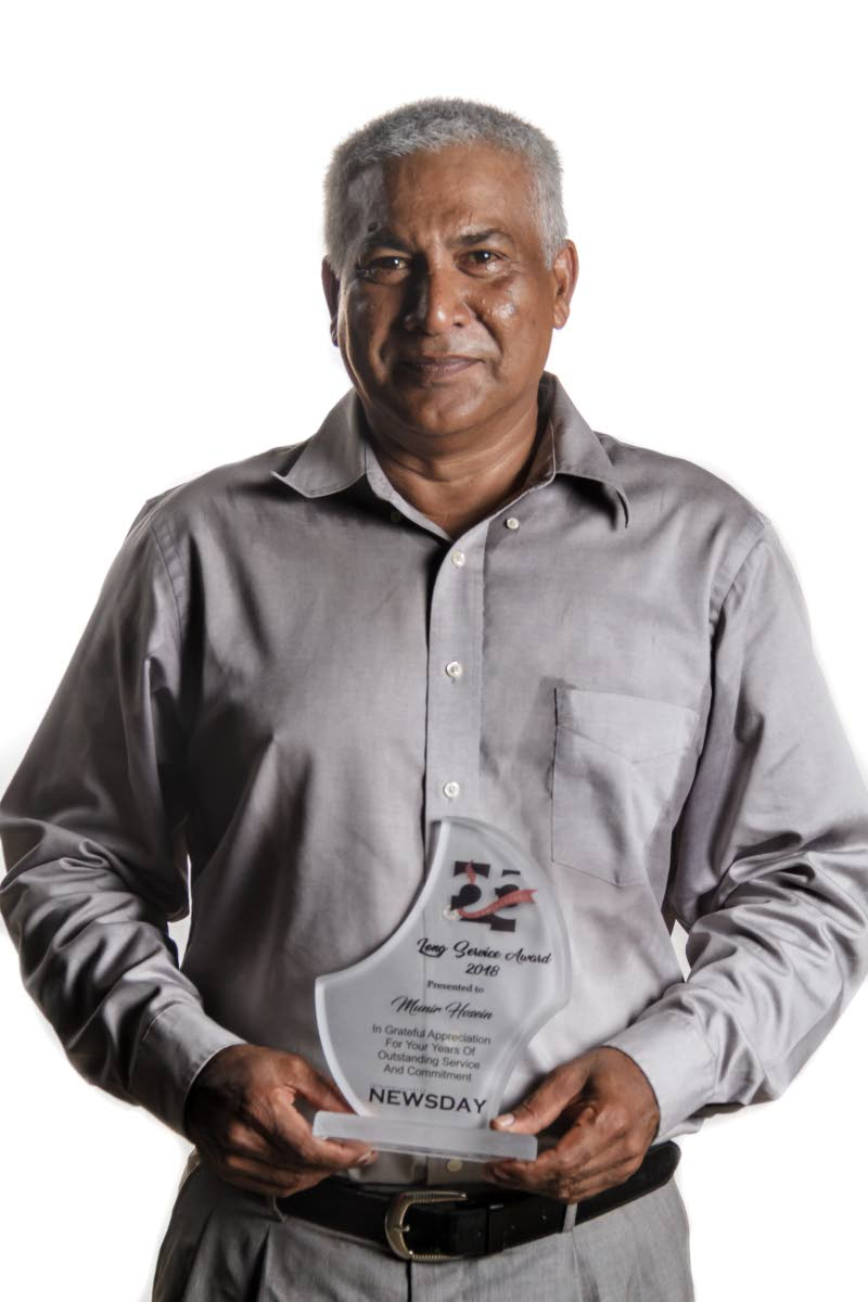 Newsday paginator Munir Hosein proudly holds his award for 20 years of service during the company's 25th anniversary celebrations in 2018.