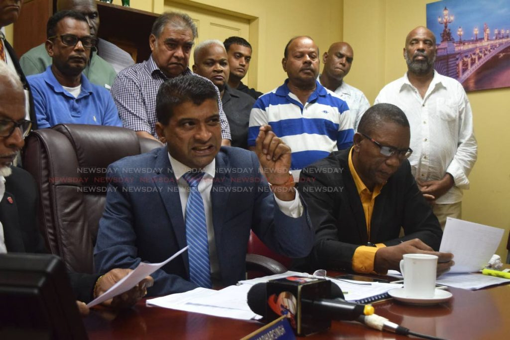 Dr Glenn Ramadharsingh, chairman of the Siparia Regional Corporation, centre, speaks to media at a press conference at the corporation yesterday while Councillor Deryck Collin Bowrin for Mon Desir, right, and corporation workers look on. PHOTO BY VIDYA THURAB