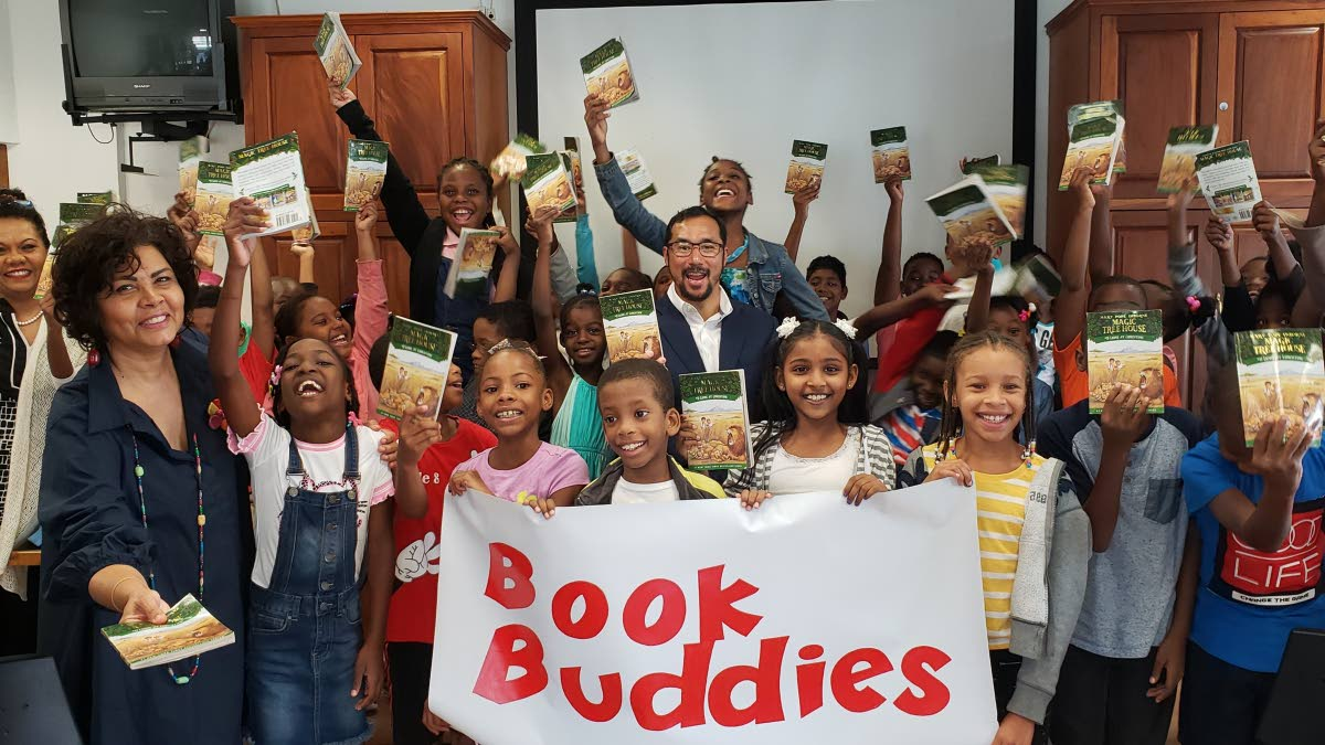 Book buddies, hold up their book Lions at Lunchtime from the Magic Tree House Series, as they celebrate their final day of the Book Buddies vacation camp at Nalis, Port of Spain.