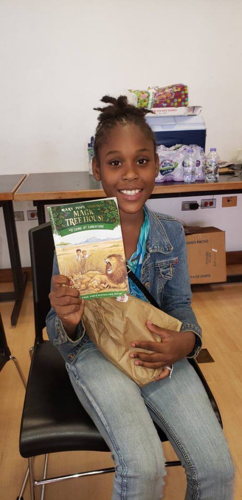 Book buddy Anissa Grant holds up her Lions at Lunchtime book at the final day of her reading camp at Nalis, Port of Spain. PHOTOS BY RACHAEL ESPINET