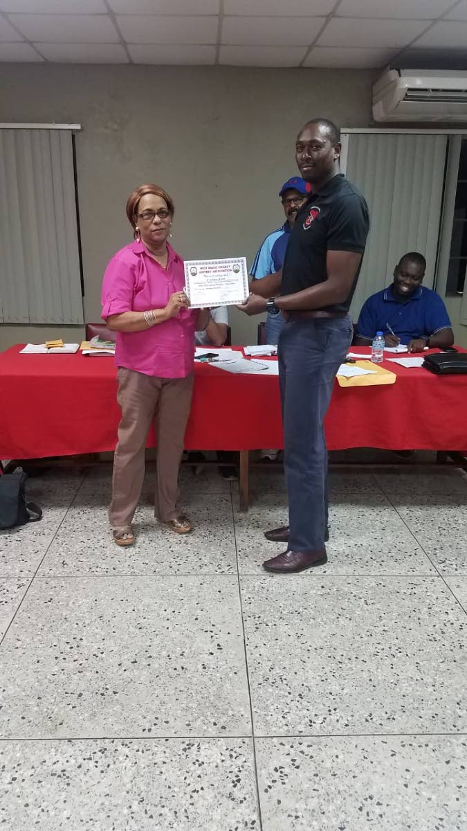 Referee Carlton Best, on the right, collects his Cricket West Indies certification from Anne Marie Charles, secretary of TT Cricket Umpires and Scorers Union two weeks ago. COURTESY PHOTO TT CRICKET BOARD